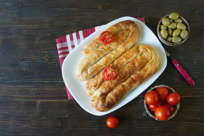 Balkan cuisine. Bureks - popular national dish - with tomatoes and olives.  Flat lay. Dark background. Free space for text. Balkan cuisine. Bureks - popular stock photos