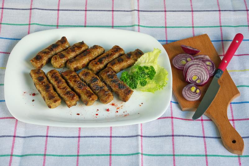 Balkan cuisine. Cevapi - grilled dish of minced meat. National dish, popular in the Balkans royalty free stock photo
