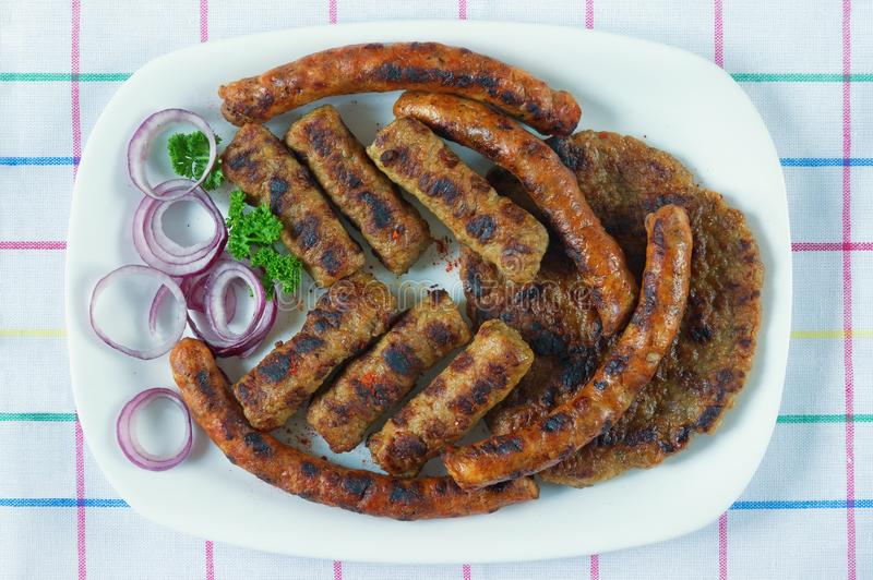 Balkan cuisine. Cevapi, kobasica and pljeskavica - grilled dish of minced meat. Flat lay. Balkan cuisine. Cevapi, kobasica and pljeskavica - grilled dish of stock images