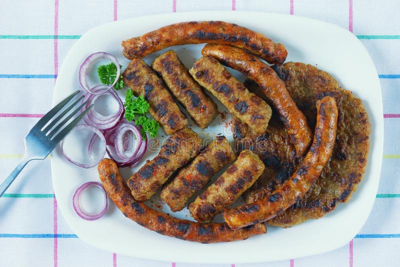 Balkan cuisine . Grilled dish of minced meat - cevapi , kobasica and pljeskavica . Flat lay royalty free stock image