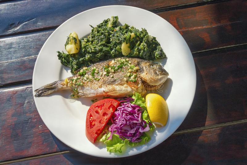Balkan keuken Geroosterde vissen met groenten op witte plaat De donkere rustieke vlakke achtergrond, legt stock foto