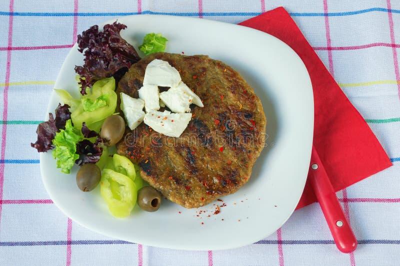 Balkan kokkonst Pljeskavica - en grillad maträtt av kött - med ost och grönsaker royaltyfria foton