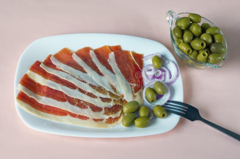 Balkan kokkonst Vit platta med skivor av prsut och gröna oliv på rosa pastellfärgad bakgrund royaltyfri foto