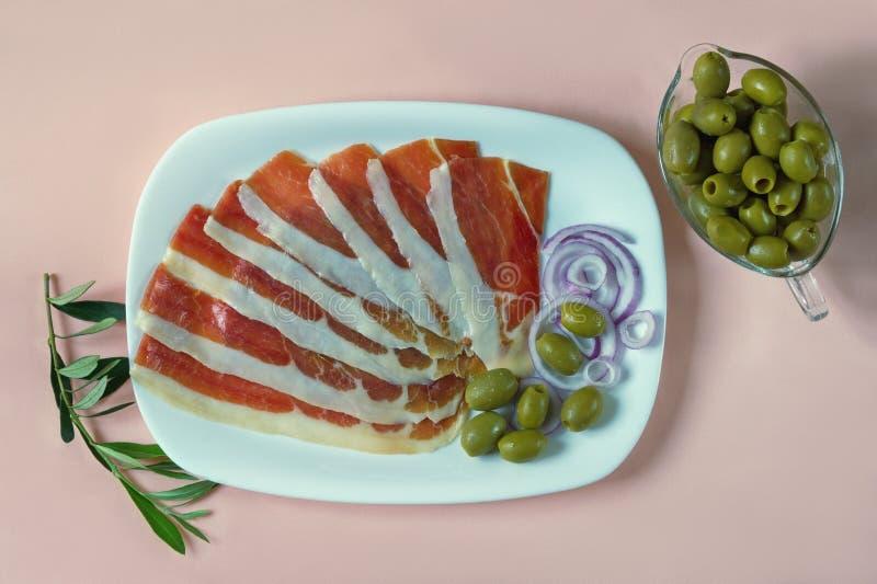 Balkan kokkonst Vit platta med skivor av prsut torr-kurerad skinka, prosciutto på rosa pastellfärgad bakgrund, lekmanna- lägenhet royaltyfri fotografi