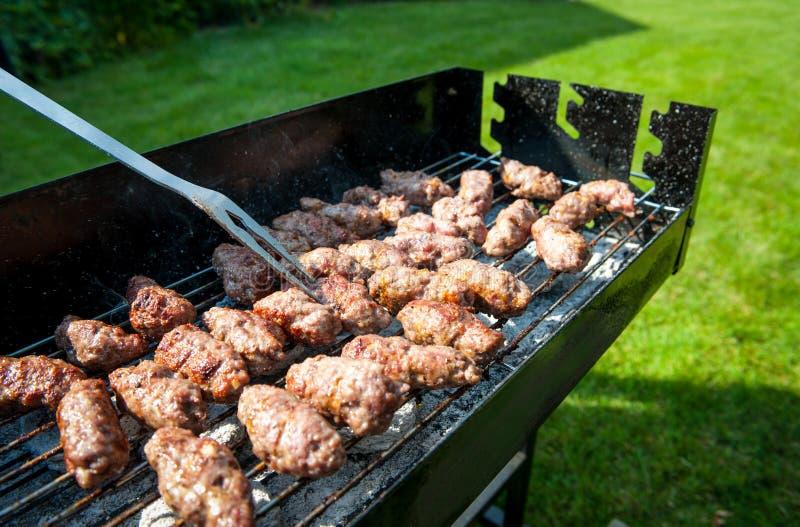 Balkan vleesballetjes genoemd cevapi op barbecue met BBQ vork stock fotografie