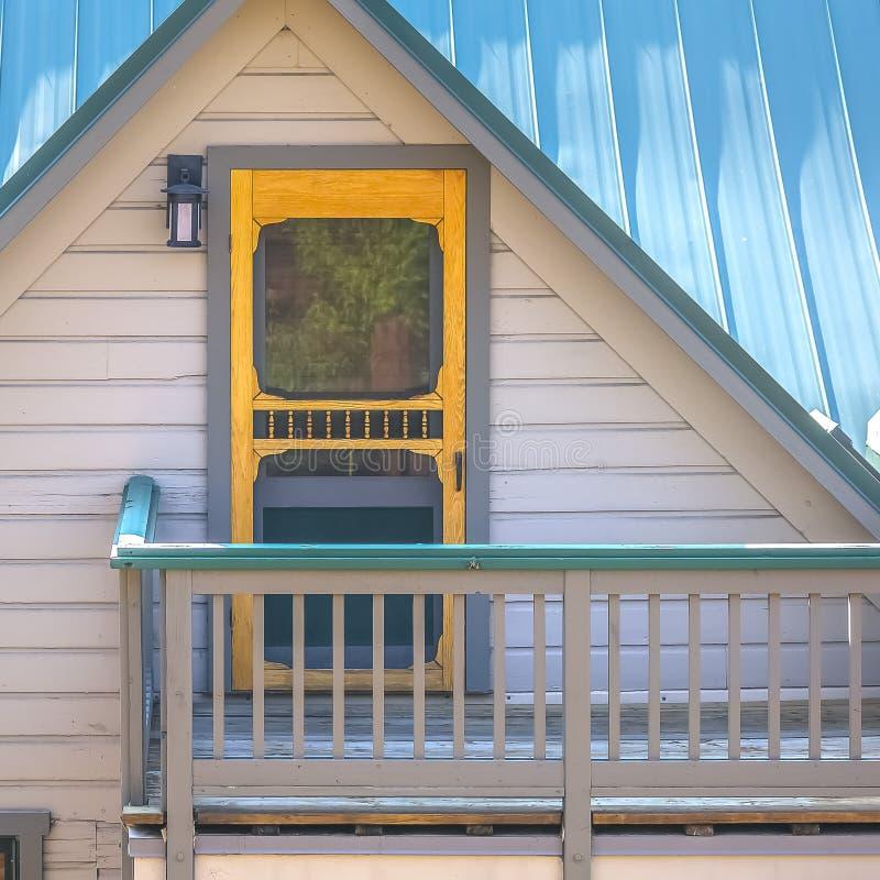 Balkon eines Dachbodens mit gelber Tür und Lampe stockfotografie