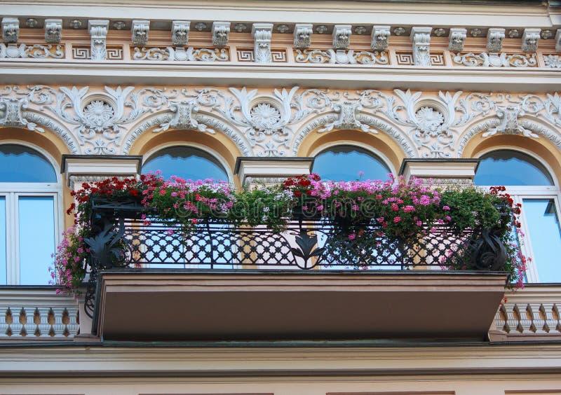 Balkon mit Blumen und Fassade des Gebäudes in klassischem styleBalcony mit Blumen und Fassade des Gebäudes stockfotos