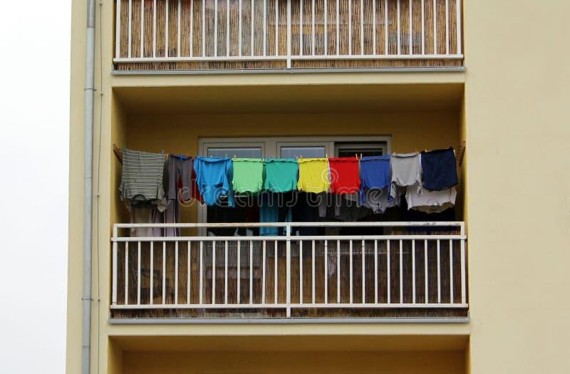 Balkon voll von bunten T-Shirts, gewaschene Kleidung trocknend lizenzfreie stockbilder