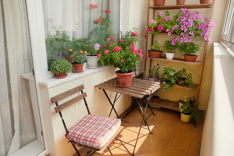Balkon z małym stołem, krzesłem i kwiatami, zdjęcie stock