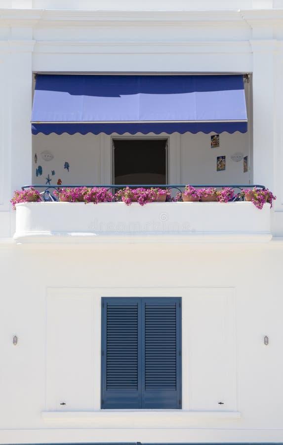 Balkong med blommor och fönstret Med den blåa markisen Vit väggbyggnad arkivfoton
