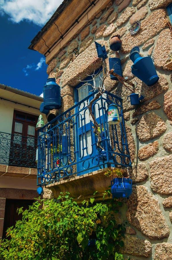 Balkong som dekoreras med massor av blåa pannor på stenhusfasad arkivbilder