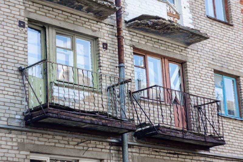 Balkonger och fönster på en gammal övergiven byggnad arkivfoton
