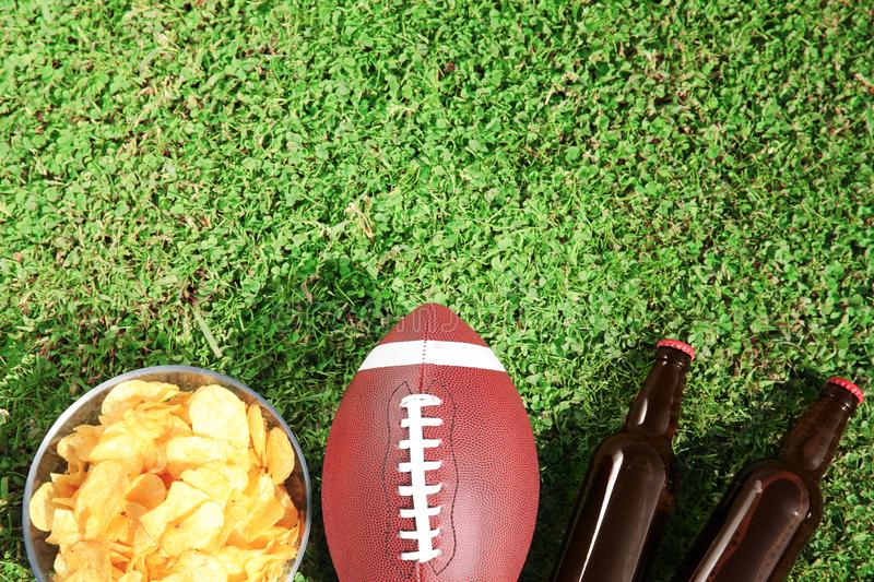 Ball for American football, beverage and chips on fresh green field grass, flat lay. royalty free stock images
