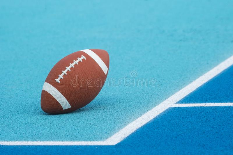 Ball for American Football on blue court, outdoor. American Football ball on a blue multifunctional sport outdoor court royalty free stock photography
