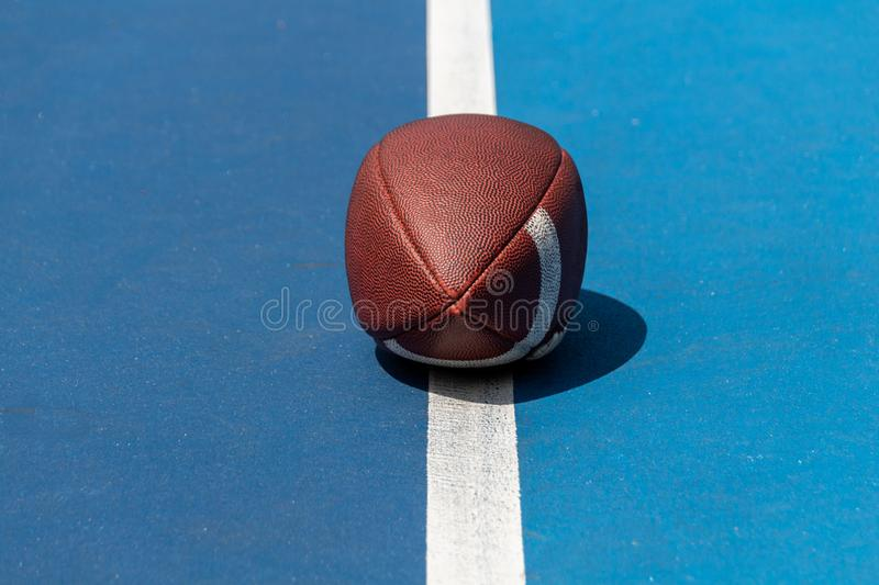 Ball for American Football on blue court, outdoor royalty free stock images