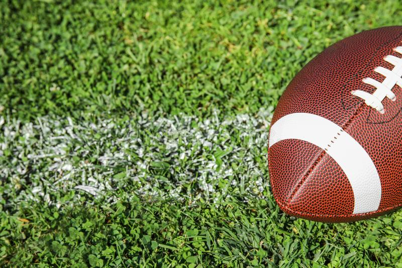 Ball for American football on fresh green field grass. Space for text royalty free stock images