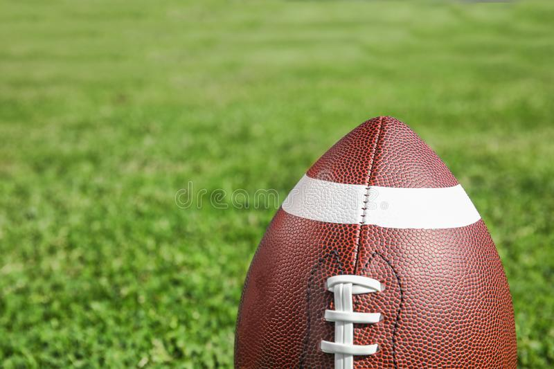 Ball for American football on fresh green field grass. Space for text royalty free stock image