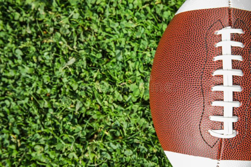 Ball for American football on fresh green field grass, top view. Space for text stock images