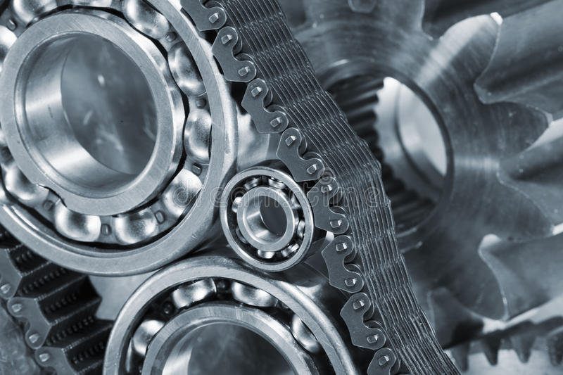 Ball-bearings and gears in close-ups. Titanium and steel parts, ball-bearings and gears in a metal blue toning concept stock image