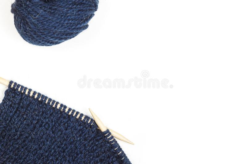 Process of knitting. Ball of blue woolen thread and knitting needle isolated background. Needlecraft backgtound royalty free stock images