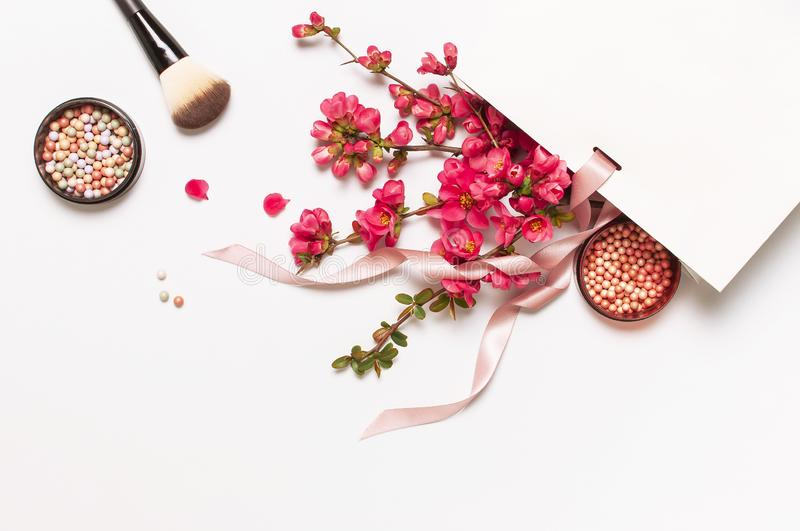 Ball blush rouge and face powder, makeup brush, spring pink flowers in white gift package on light background top view flat lay. royalty free stock photo