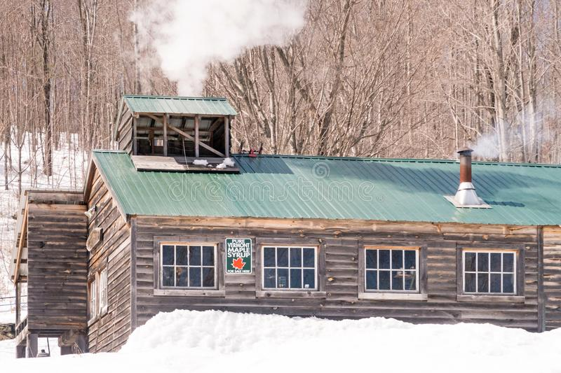 Ball Brook Maple Sugar Shack. In Pownal Vermont, in March, springtime harvest making syrup, New England with smokestacks and snow stock photo