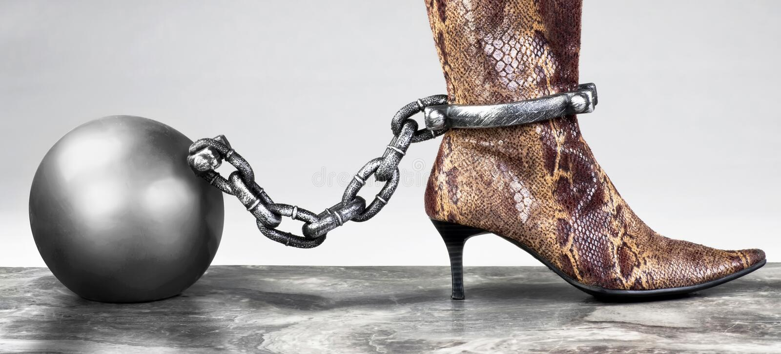 Ball and Chain. Lady in snakeskin boots locked with ball and chain royalty free stock photos