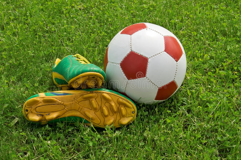 Ball and cleats. Is on the soccer field stock image