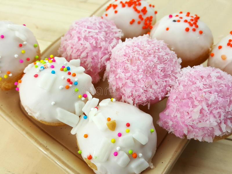 Ball donuts scatter over of colorful sugar. stock image