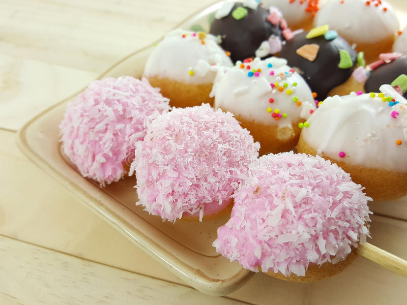 Ball donuts scatter over of colorful sugar. stock images