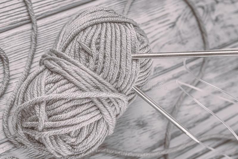 Ball of gray yarn and knitting needles on the gray background stock photography