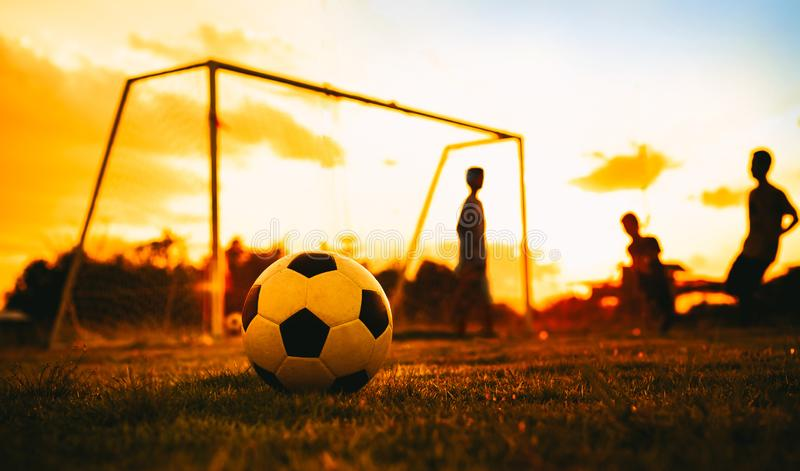 A ball on the green grass field for soccer football game under the sunset ray light and rain.Silhouette action sport picture.An ac stock images