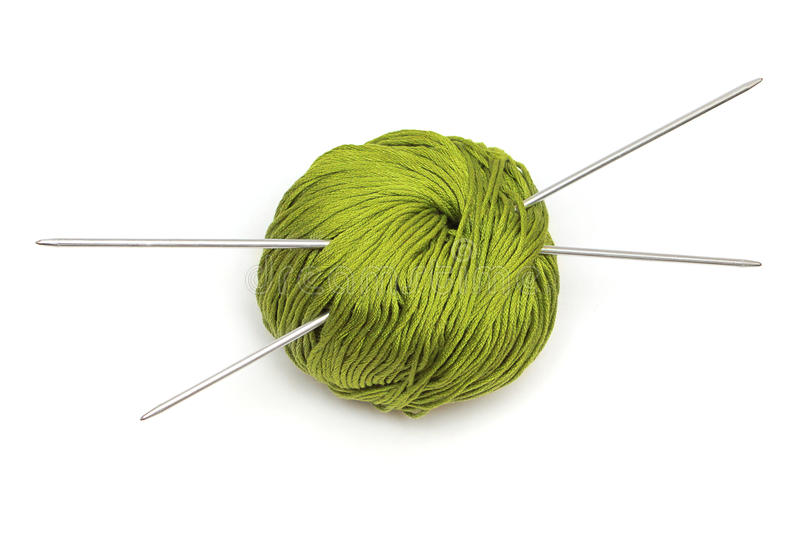 Ball of green wool with knitting needles stock photography
