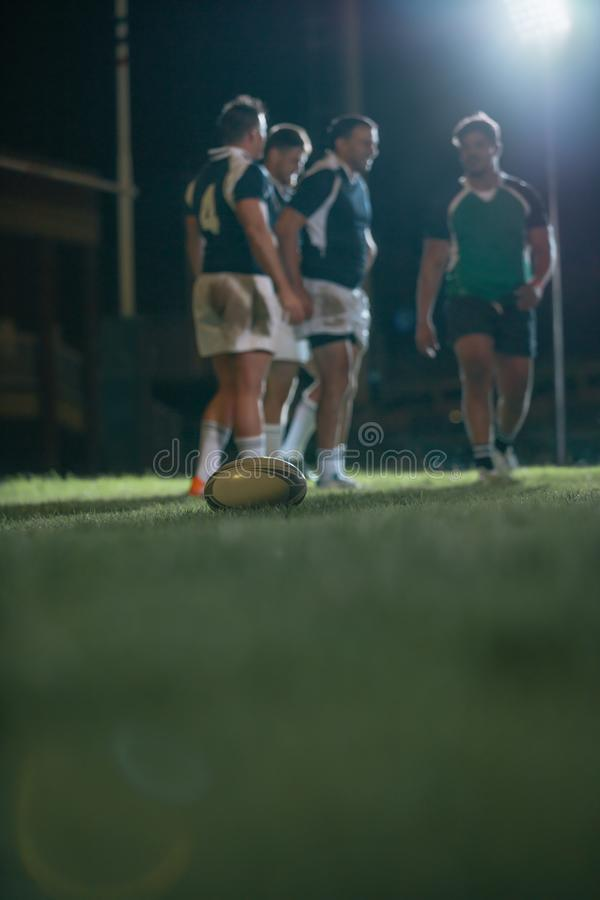 Ball on ground during rugby match. Ball on grass field with players in background. Ball on ground with teams at the back during the rugby match royalty free stock image