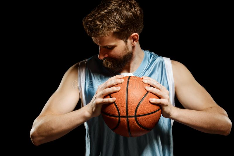 Ball in hands of player. Basketball player squeezing a ball between hands and looking down, isolated on black stock image