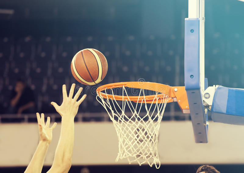 Ball in hoop at basketball game. Basketball players hands royalty free stock images