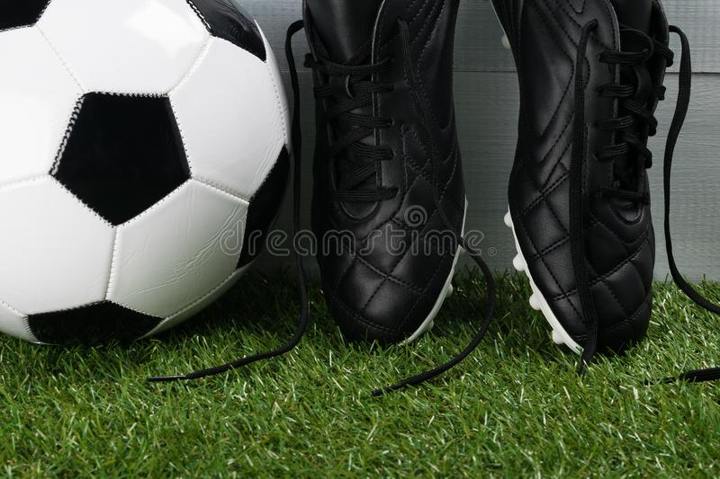 Ball and leather shoes for soccer player close-up on green grass stock images