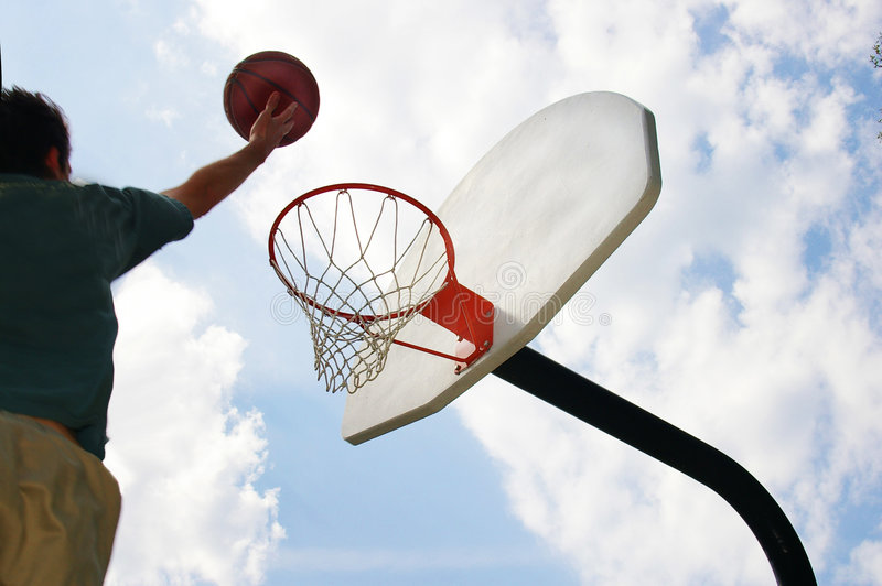 Ball player. Basketball player jumping up toward the hoop royalty free stock photo