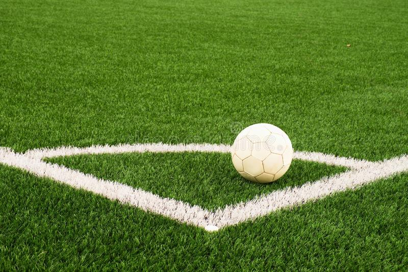 Ball prepared for corner kick. Heated football playground. corner on artificial green turf ground with painted white line marks. Milled black rubber in basic stock photography