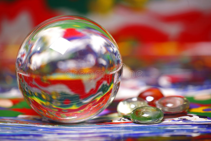 Ball reflecting paint colors. Ball reflecting colors of abstract painting; stones of colored glass lie to right side and also reflect light royalty free stock images