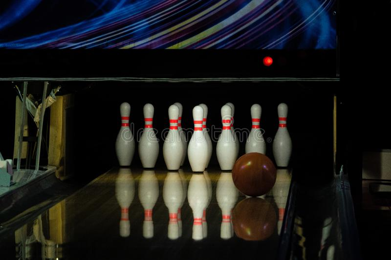 Ball rolling on the right side a bowling alley lane with pins.  stock photo