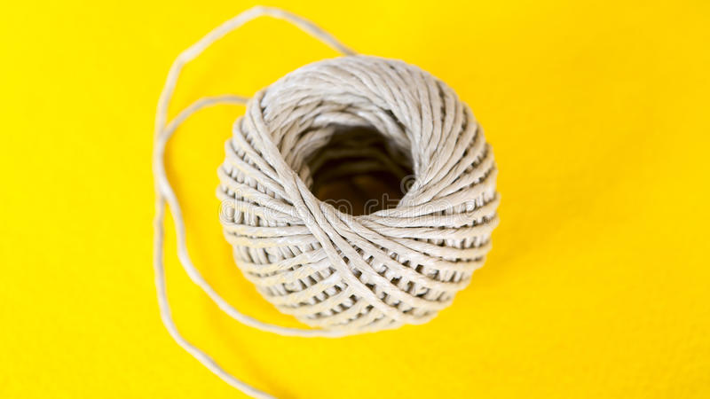Ball of rope on yellow table stock images