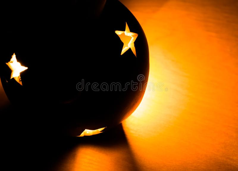 Ball shaped christmas lantern illuminated by warm light of candle from inside with cutouts in shape of stars. stock image