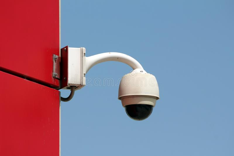 Ball shaped rotatable waterproof security camera CCTV mounted on side wall of red office building royalty free stock photo