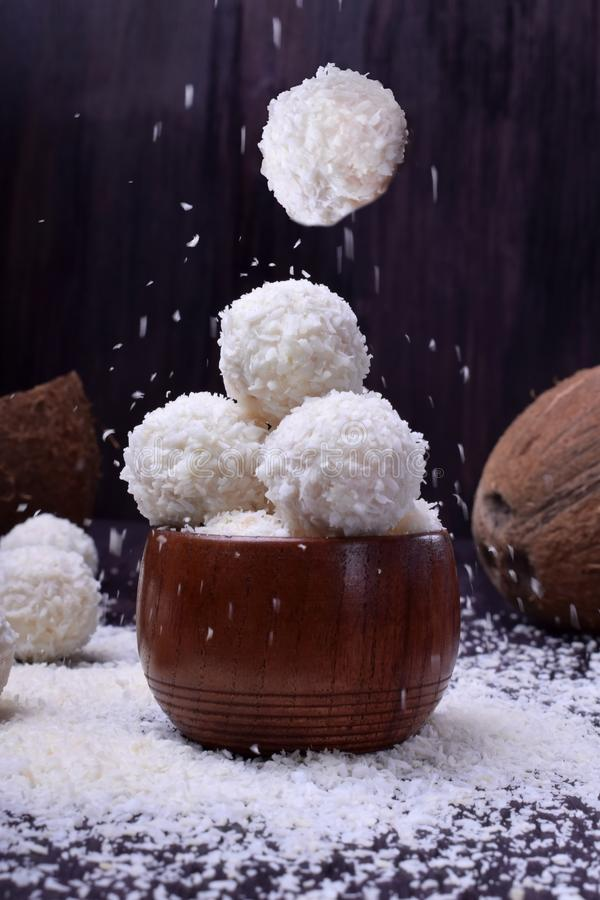 Ball shaped white sweets are sprinkled with coconut flakes. Against the dark background stock photo