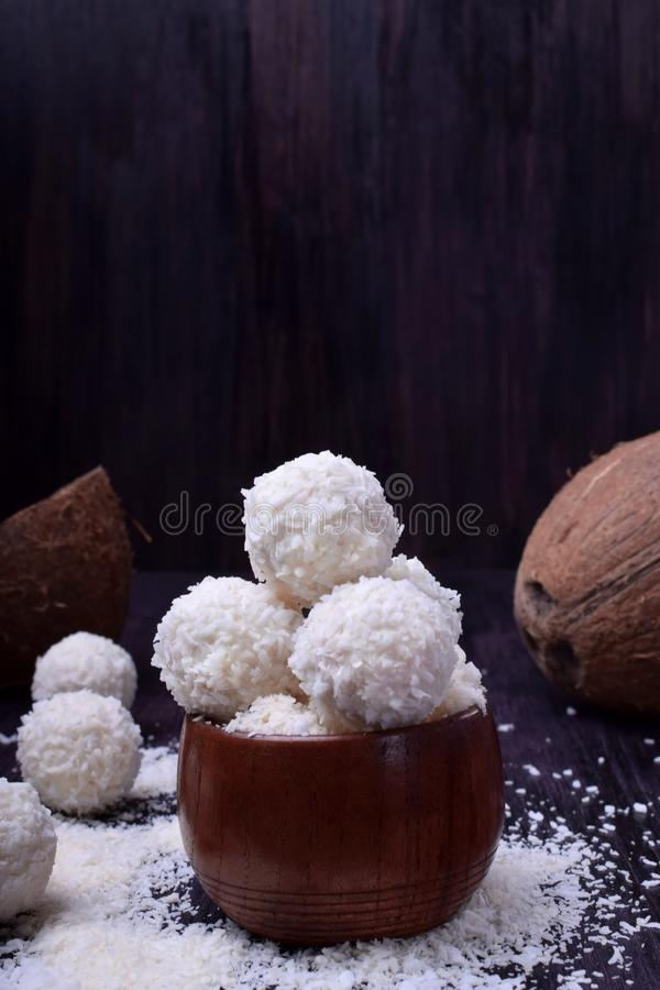 Ball shaped white sweets are sprinkled with coconut flakes. Against the dark background royalty free stock photos