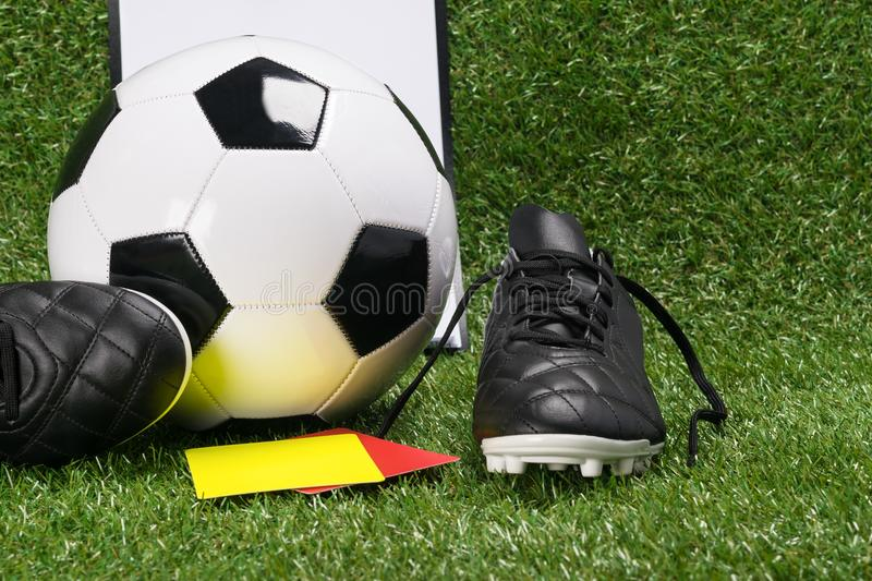 Ball and shoes for football with a yellow and red card of the referee, on a green lawn royalty free stock photos