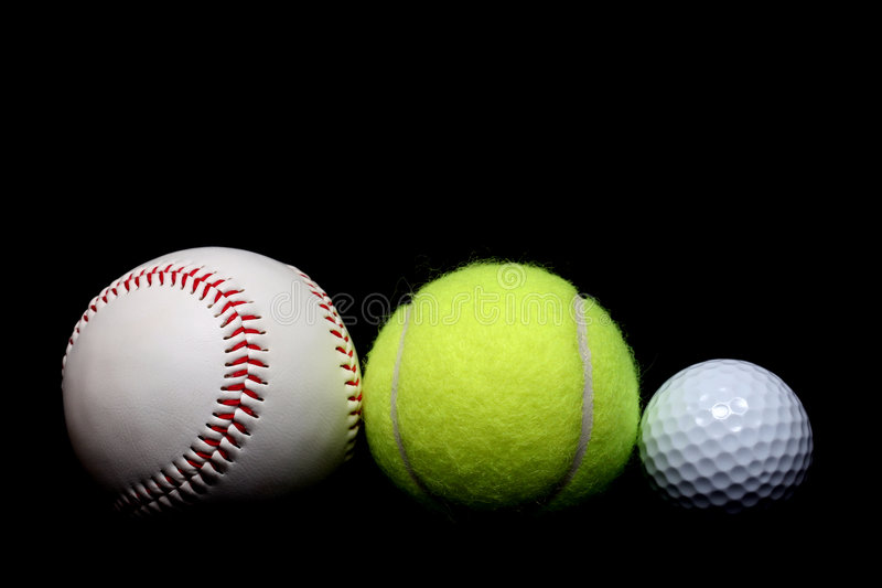 Ball sports. A base ball, tennis ball, and golf ball side by side, close up over black royalty free stock photography