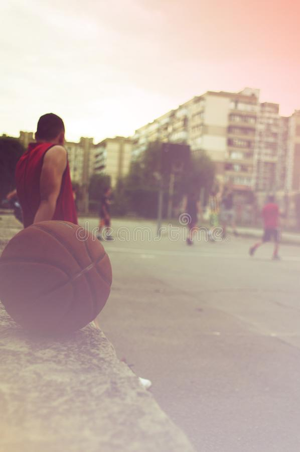 The ball on the sports ground. Active basketball game. The man looks like a basketball team plays.  royalty free stock image