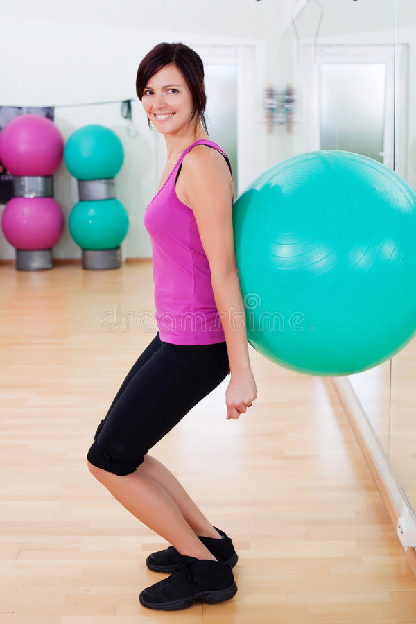 Ball squat. Woman dressed sportswear exercising making a fitball squat royalty free stock image
